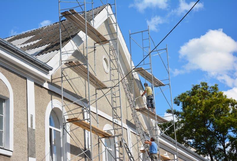 涂灰泥房子门面的承包商室外 绘画和涂灰泥有石棉屋顶修理的外部房子脚手架墙壁 免版税库存图片