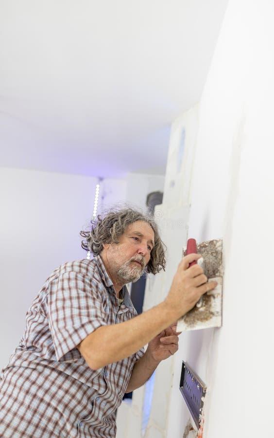 涂灰泥白色的中年人工作者、建造者或者房主 免版税图库摄影