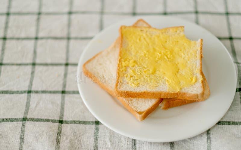 涂黄油的面包在桌衣裳和某人的白色板材上把放叮咬面包的小片断在角落 库存图片