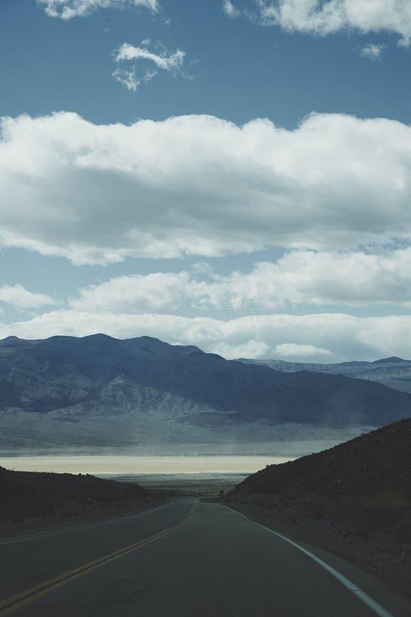 消失入沙漠山风景的路 库存图片