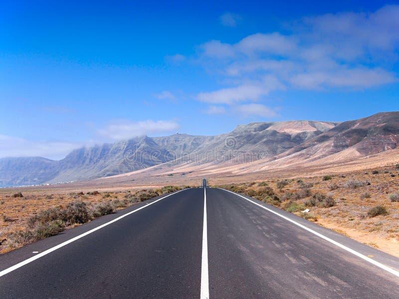 消失在天际的柏油路通过火山山山坡 蓝色覆盖天空白色 兰萨罗特岛 库存图片