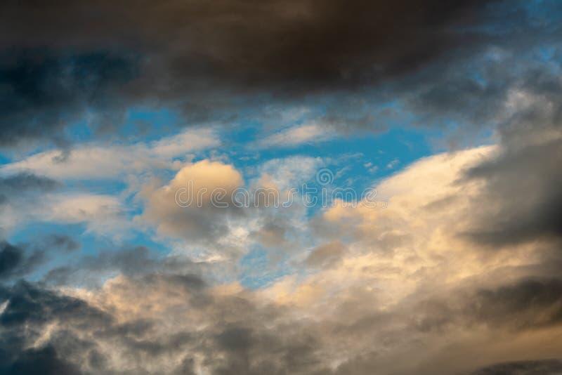 消失的光芒照亮的金黄蓬松云彩在漂浮横跨晴朗的天空蔚蓝的日落和剧烈的黑暗的雷云 免版税库存图片