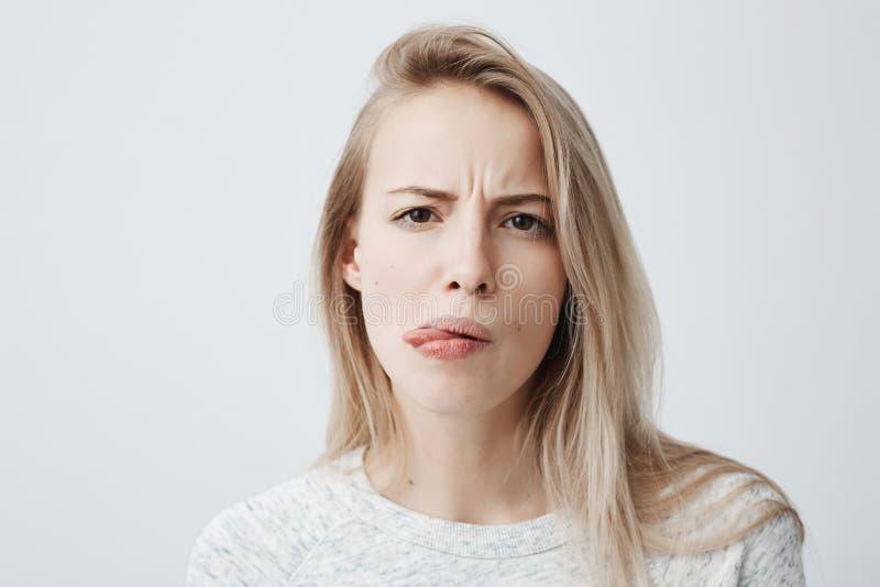 消极人的反应、感觉和态度 恶心的过于拘谨白肤金发的妇女特写镜头画象便衣的 库存照片