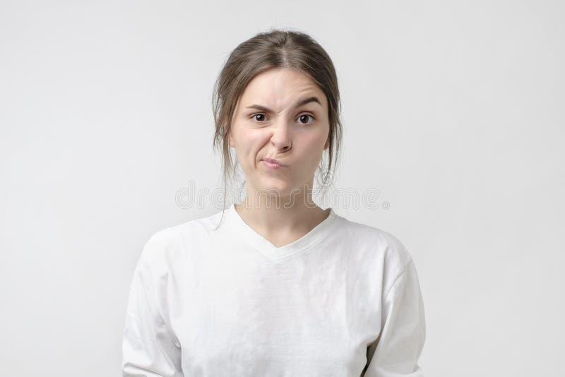 消极人的情感和感觉 脾气坏的年轻,皱眉的眼眉、她的表示的神色和的鬼脸愤怒 图库摄影