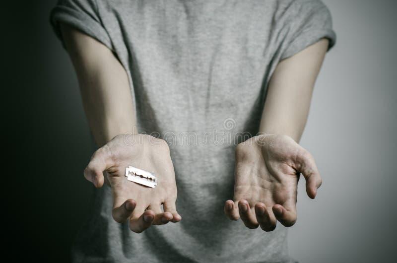 消沉和自杀题材:供以人员拿着剃刀对在灰色背景的自杀在演播室 库存图片