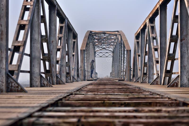 消沉的哀伤的少年坐桥梁在日落 免版税库存图片