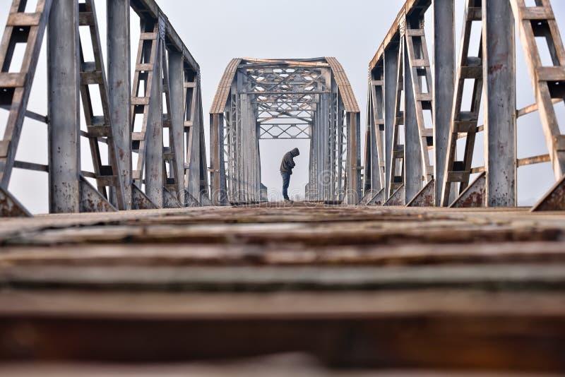 消沉的哀伤的少年坐桥梁在日落 库存照片