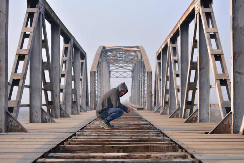 消沉的哀伤的少年坐桥梁在日落 库存图片