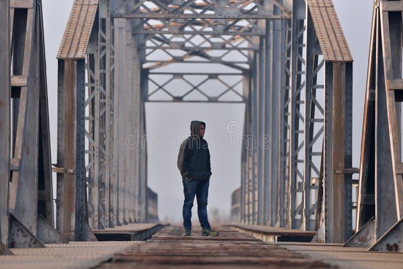 消沉的少年坐桥梁在日落 免版税图库摄影