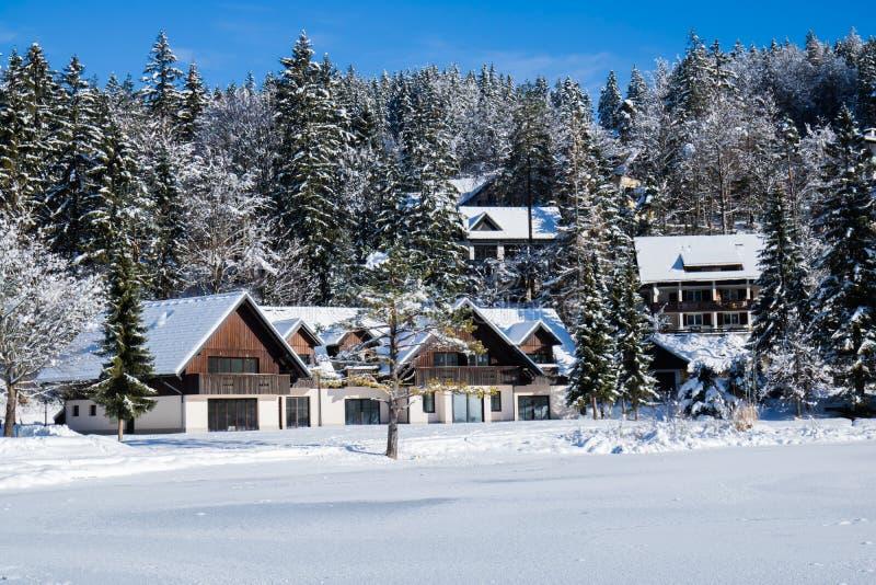 消费寒假概念在降雪的田园诗木房子里在湖,克拉尼斯卡戈拉,斯洛文尼亚旁边 库存图片