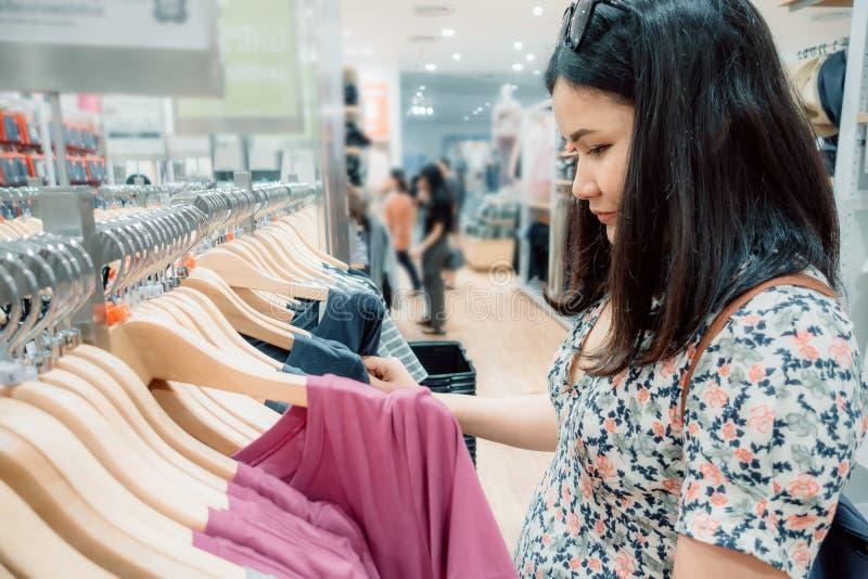 消费者至上主义妇女是幸福,当购物在百货店时穿衣,选择在机架的年轻女人画象衣裳  图库摄影