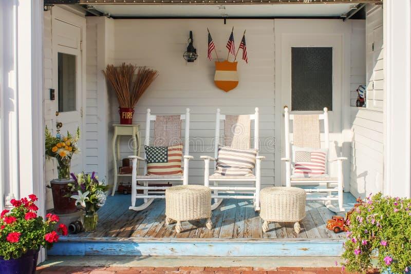 消防员和爱国主题的破旧的木前沿在有三个白色摇椅的鳕鱼角和枕头和柳条脚 免版税库存照片