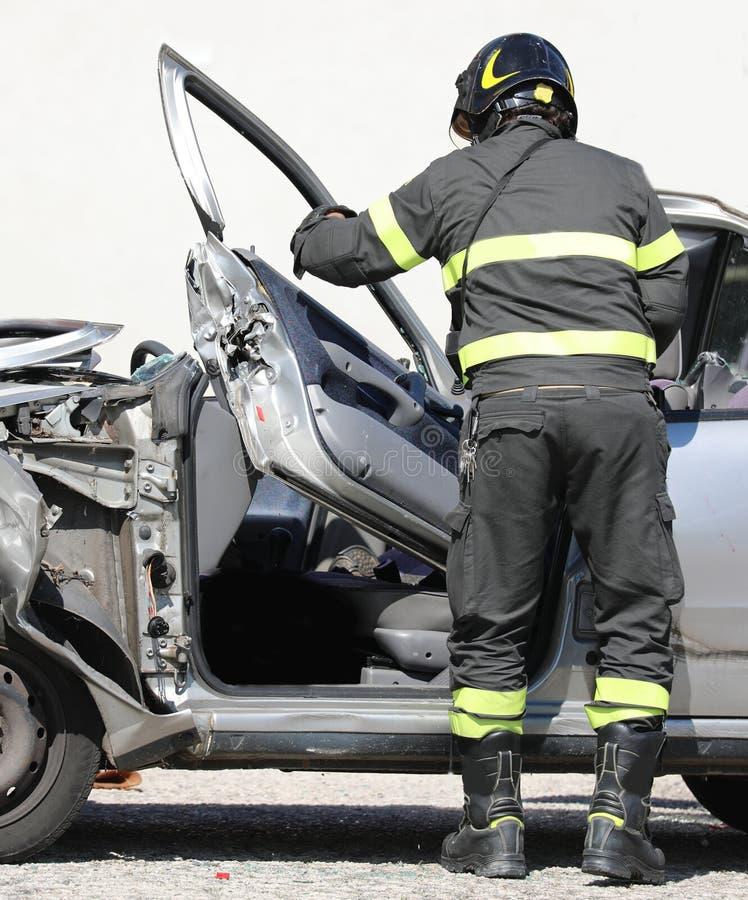 消防员在交通事故以后去除一辆被破坏的汽车的门 免版税库存照片