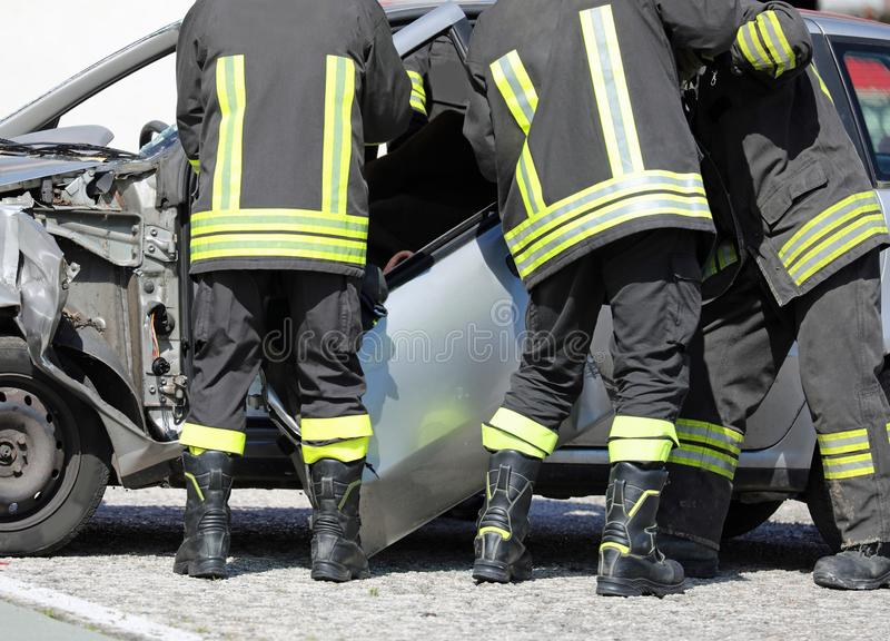 消防员在交通事故以后去除汽车的门恢复 免版税库存图片