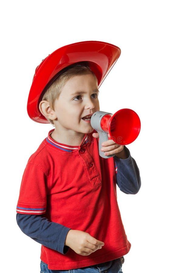 消防员服装的逗人喜爱的年轻男孩 库存图片