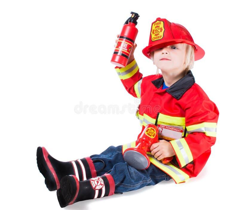 消防员服装的滑稽的男孩以去的盔甲边 免版税库存图片