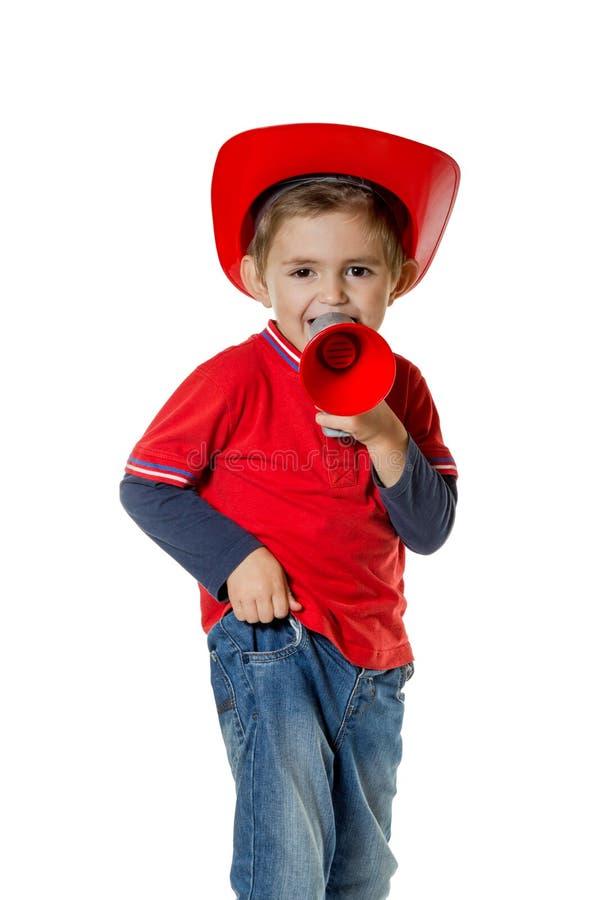 消防员盔甲的逗人喜爱的年轻男孩 免版税库存照片