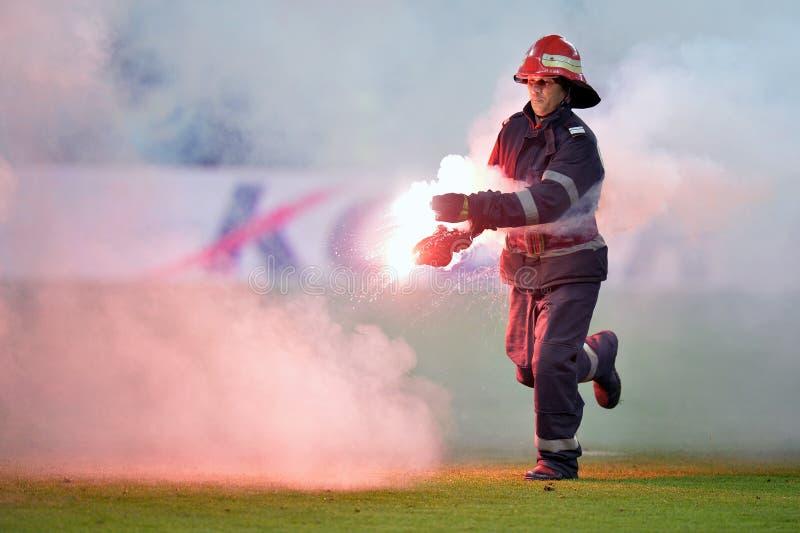 消防员从橄榄球球场去除火光 免版税图库摄影