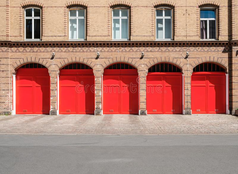 消防队与红色门和空的街道的builidng门面 免版税库存图片