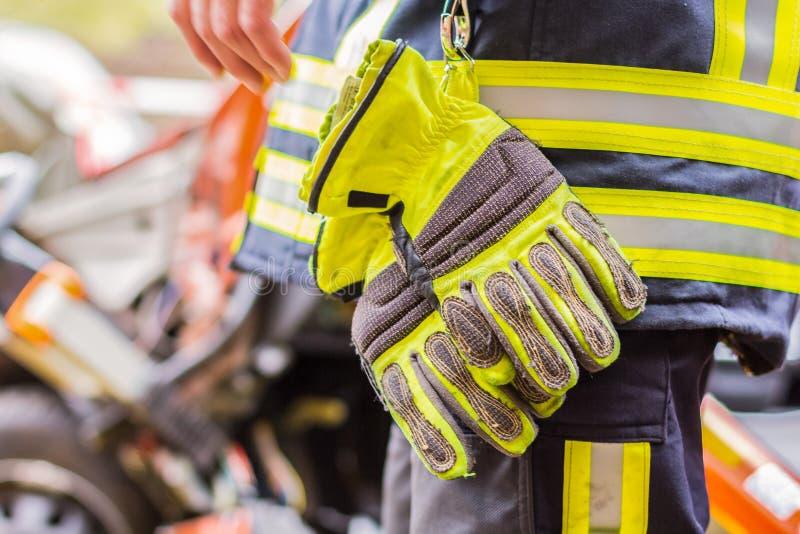 消防队员与在一辆被碰撞的汽车的专业工具一起使用 库存图片