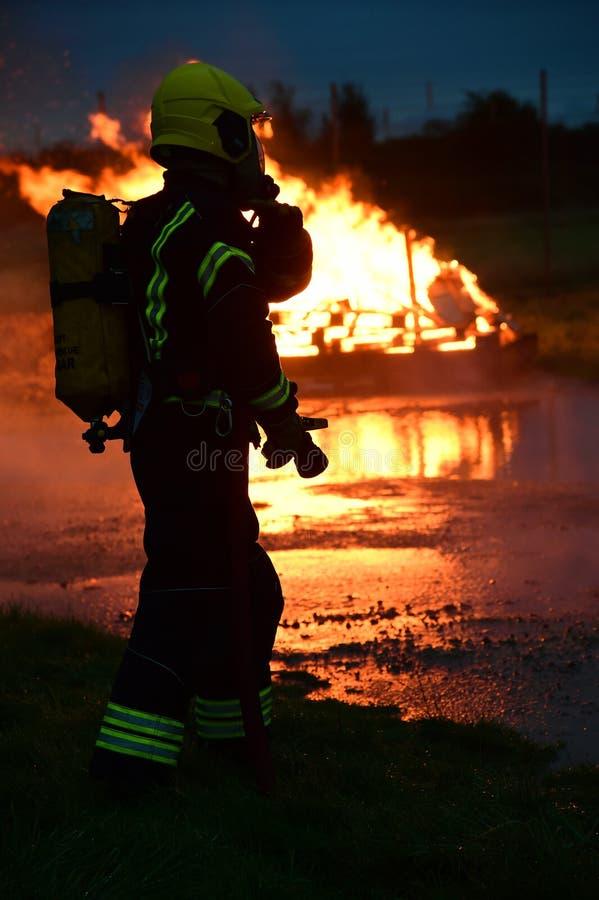 消防队员准备在晚上冲洗火 免版税库存图片