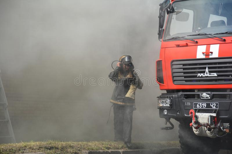消防队员剪影和救火车在烟 库存图片