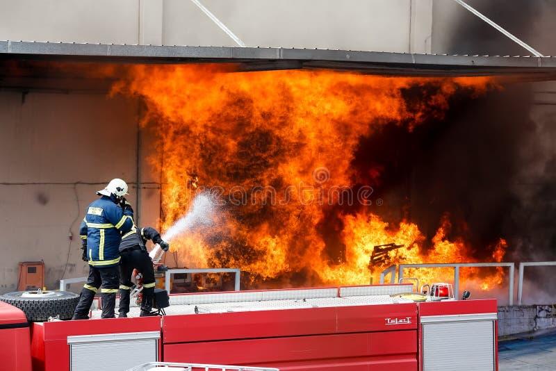 消防队员努力熄灭发生在a的火 免版税图库摄影