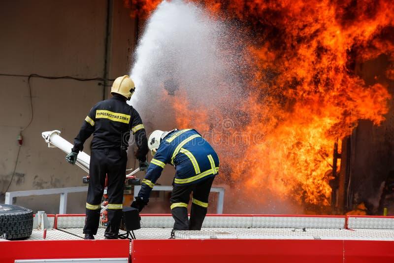 消防队员努力熄灭发生在a的火 免版税库存图片