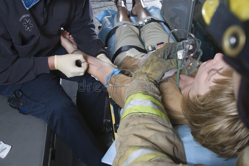消防队员和EMT Helping An Injured Patient医生 免版税库存图片