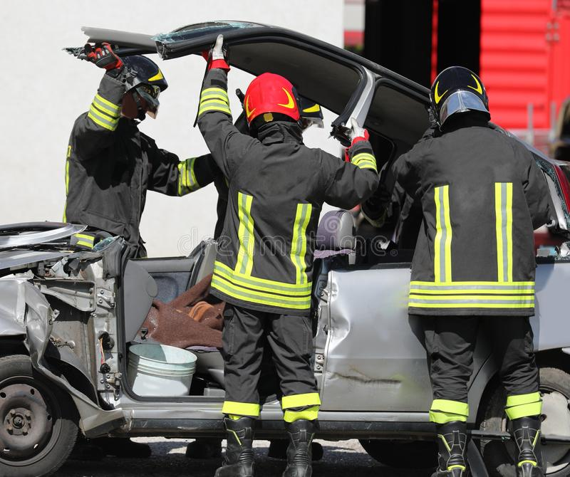 消防队员在公路事故以后打开一辆残破的汽车 免版税库存照片