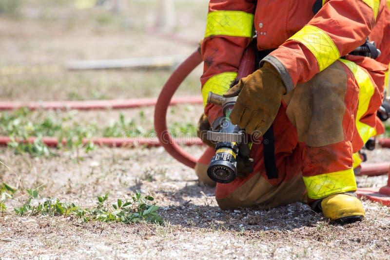 消防队员备用与消防队员搜寻的灭火水龙带 库存图片