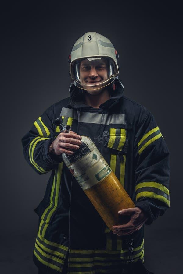 消防队员抢救拿着黄色氧气罐 免版税库存照片