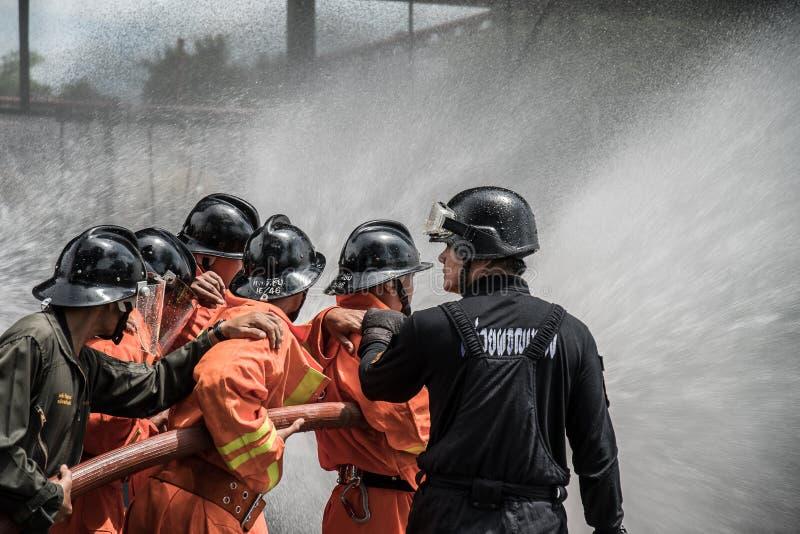 消防队员排练消防计划在LPG存贮设施 免版税库存照片