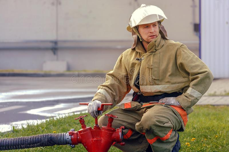 消防队员松开消防栓阀门通过水管供应水 白男性救生员画象防护服装的 免版税库存图片