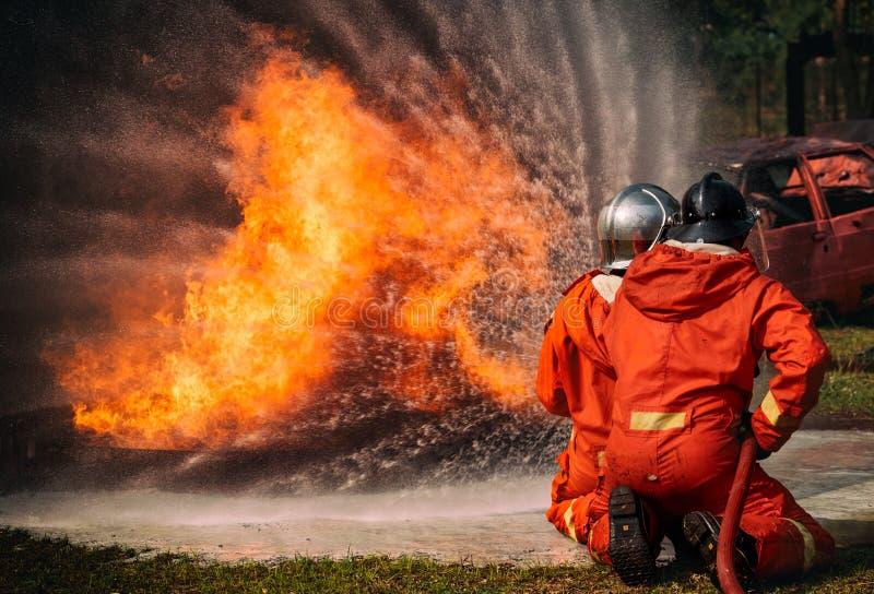 消防队员由高压喷管的喷水在火, 免版税库存照片