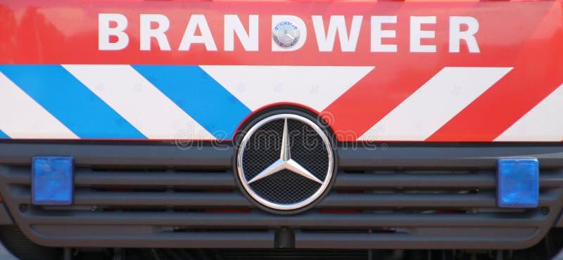 消防队的卡车前面在荷兰叫在红色汽车的Brandweer有蓝色和白色脱模的 库存照片