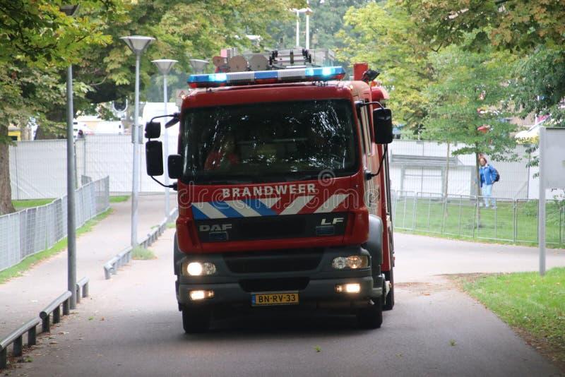 消防队的卡车在海牙驾驶与警报器和蓝色光 库存图片