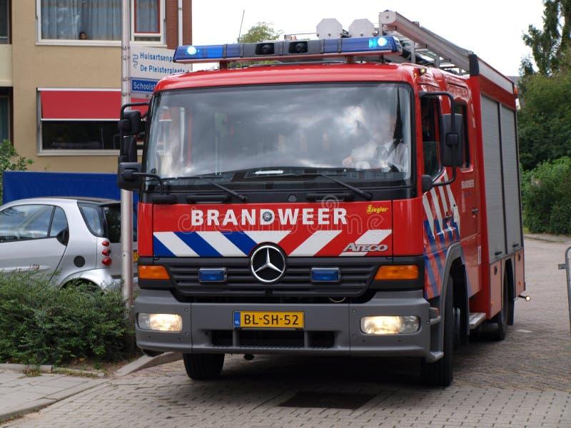 消防队的Ttruck在荷兰叫在红色汽车的Brandweer有蓝色和白色脱模的 免版税库存照片