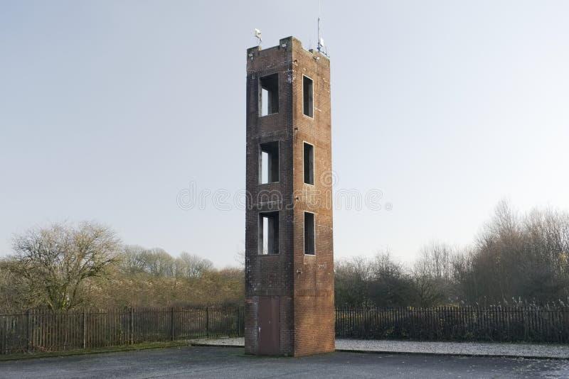 消防队紧急训练的塔实践和梯子反对红砖设施和空白的天空 免版税库存图片