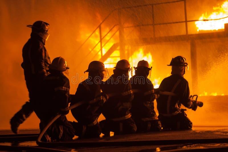 消防队长和消防队员在一个灼烧的结构前面在消火锻炼期间 免版税图库摄影