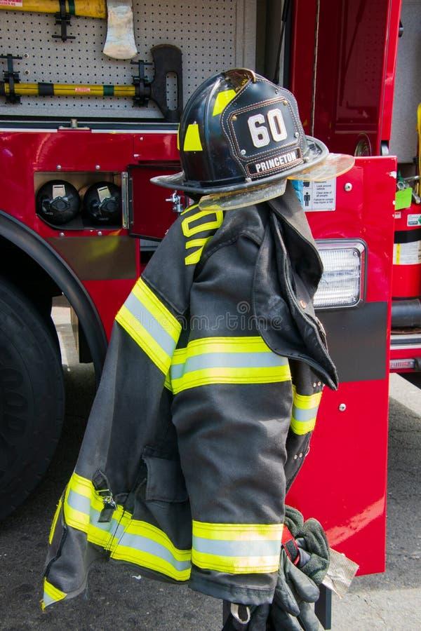 消防齿轮包括盔甲和夹克在普林斯顿艺术节的消防车显示附近被显示了 免版税库存图片
