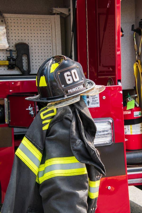 消防齿轮包括盔甲和夹克在普林斯顿艺术节的消防车显示附近被显示了 图库摄影