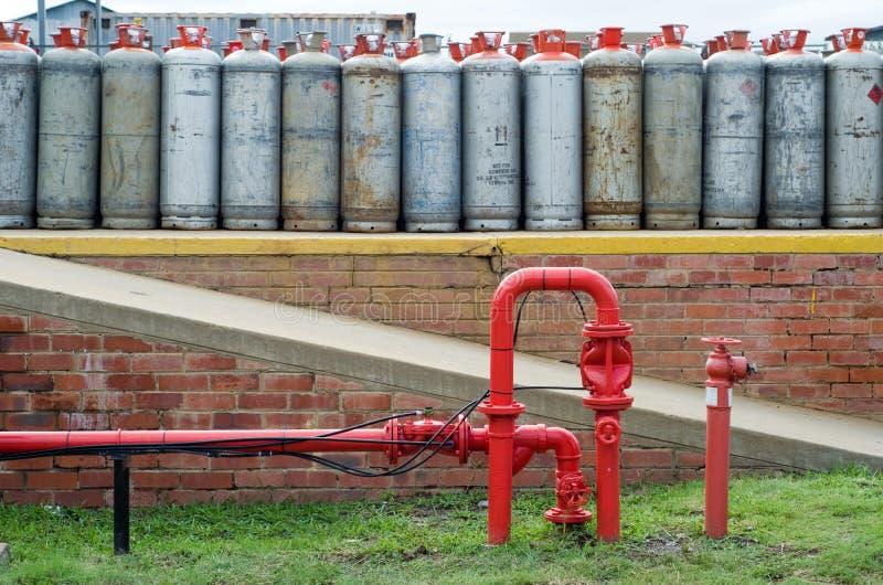 消防龙头在lpg制冷剂瓶前面的水管 免版税库存照片