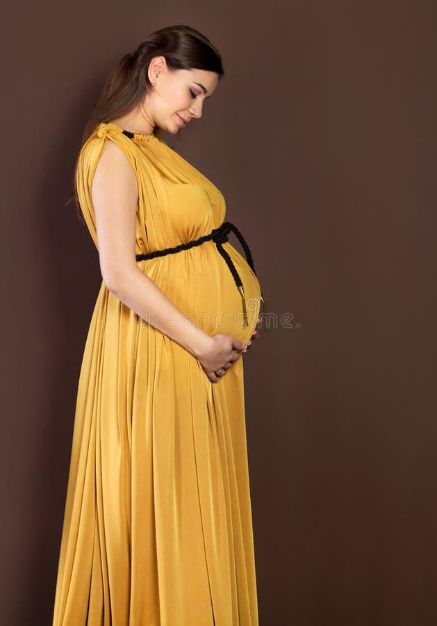 涉及她的腹部的愉快的孕妇 免版税库存照片