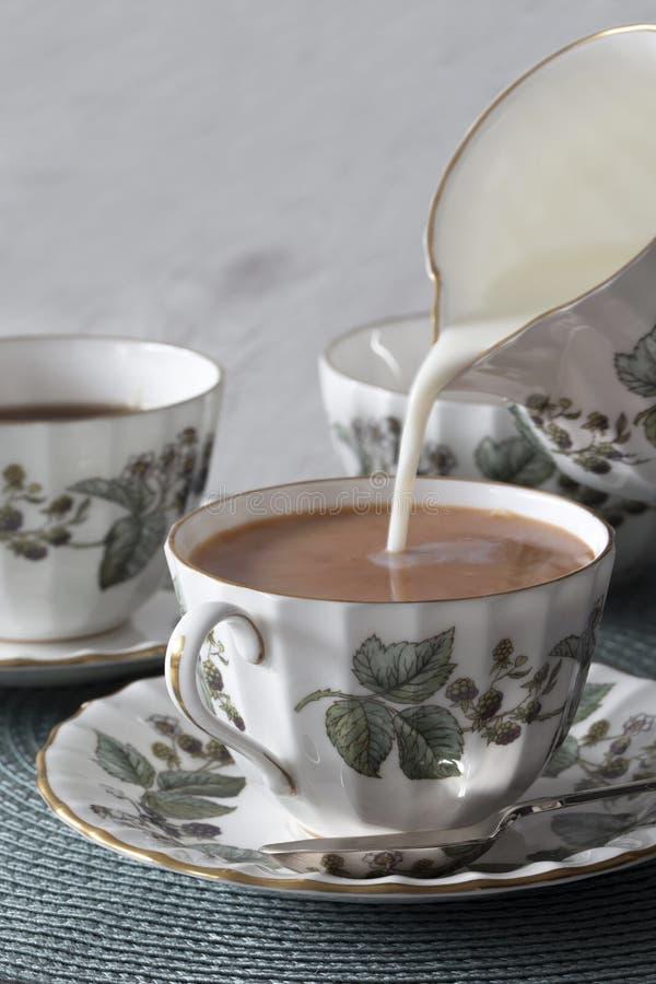 涌入一杯茶的牛奶在瓷茶具的在一绿色placemat 库存图片