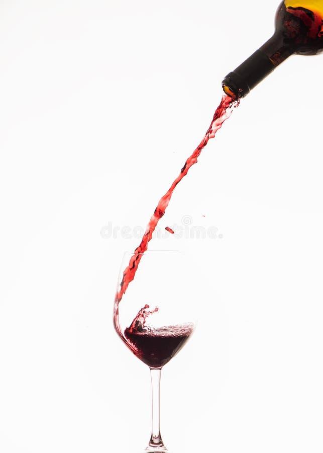 涌入下来酒杯的红葡萄酒 库存图片