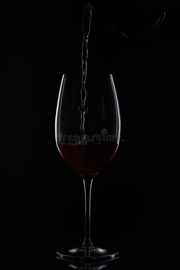 涌入从在黑背景隔绝的瓶的玻璃的红葡萄酒特写镜头射击 免版税库存图片