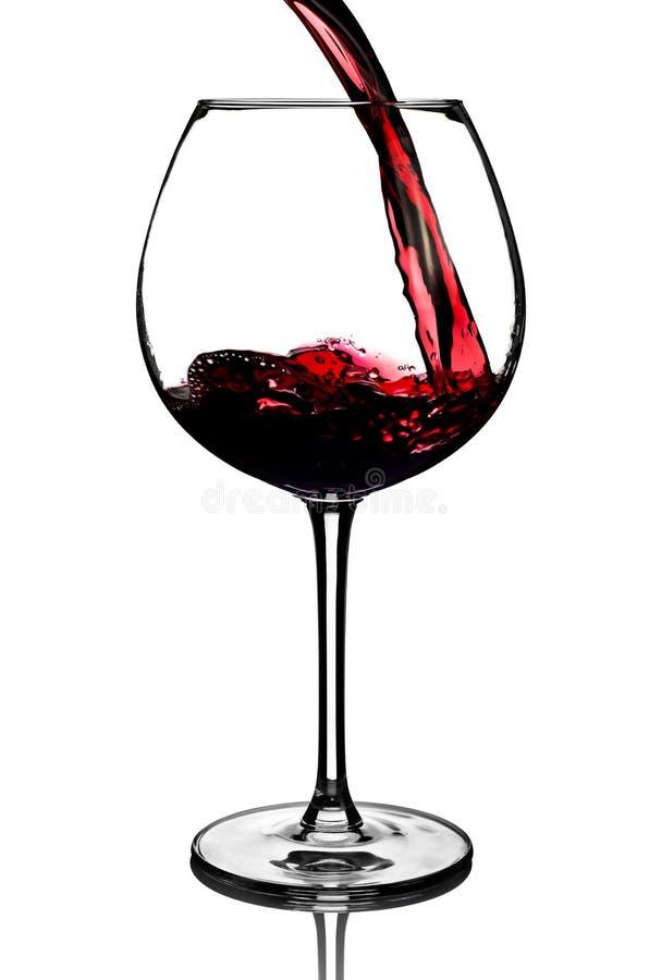 涌入在白色背景的玻璃的红葡萄酒 库存照片