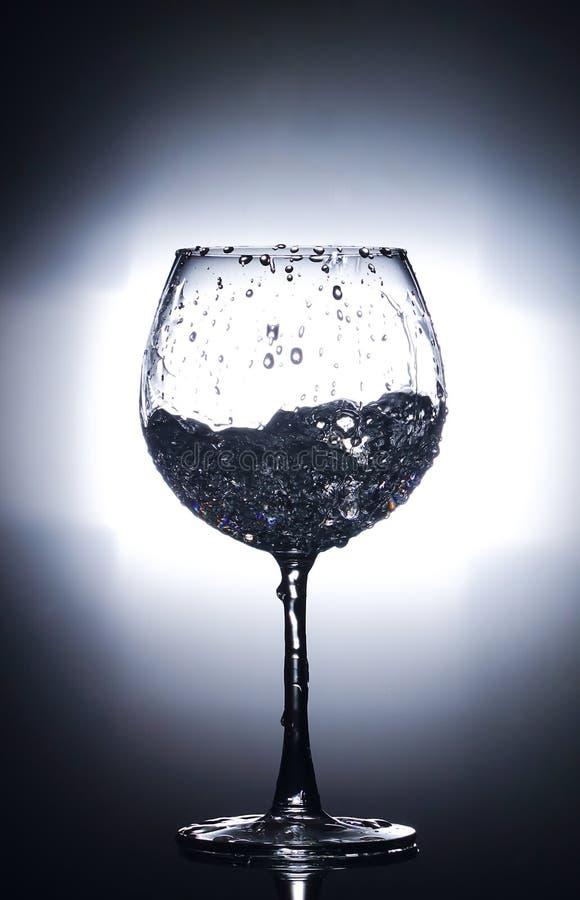涌入玻璃的水 隔绝在明亮的白色和黑背景 图库摄影