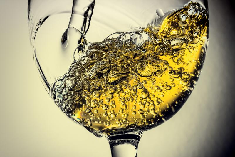 涌入玻璃,白葡萄酒飞溅特写镜头的白葡萄酒小河 与酒的颜色的黑白照片 库存图片
